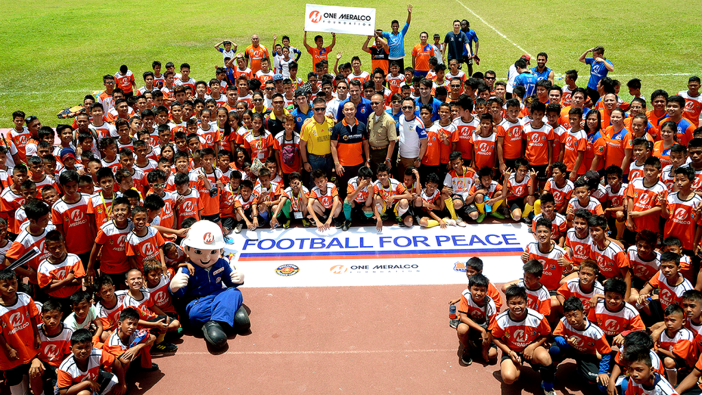 Participants of One Meralco Foundation and the Philippine Marine Corps' Football for Peace Festival 2015 pose for a photo op at the University of Makati Stadium.
