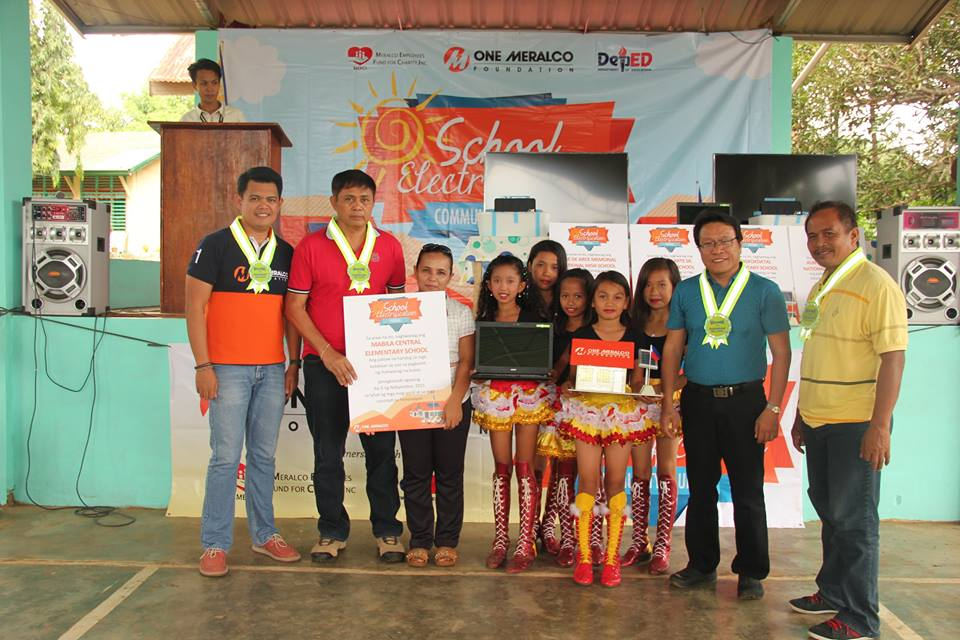 OMF Program Manager for School Electrification Rainier Manguiat with the teachers and students of Balut Island.