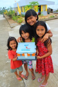 Children hold a scale model of one of the 266 concrete houses donated by the MVP group of companies to victims of Typhoon Pablo in Baganga, Davao Oriental. One Meralco Foundation, the social development arm of Meralco, a member of the MVP group, funded the extension of the electrical facilities of the Davao Oriental Electric Cooperative (DORECO) to reach the newly established community.