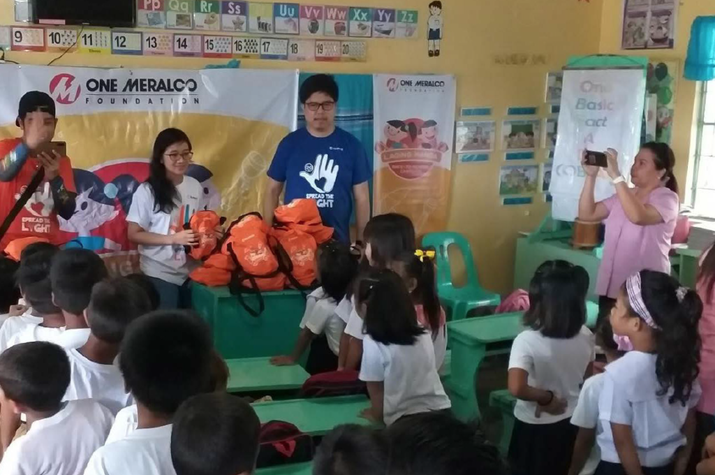 Engr. Maria Trixie Pescos (second from left) distributes back to school kits to students of Pugad Elementary School in Hagonoy, Bulacan.