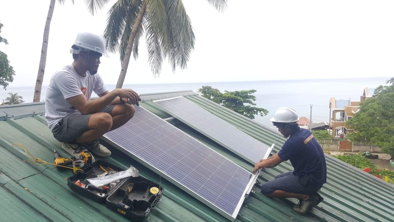One Meralco Foundation engineers install a solar panel on the roof of an island school in Samar.